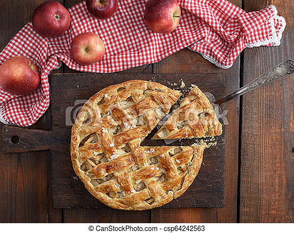 baked traditional fruit cake on a brown wooden board - csp64242563