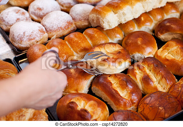 Bakery Worker's Hand Picking Up Bread With Tong - csp14272820