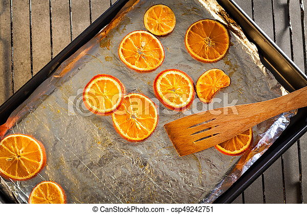 Baking fresh orange slices, to dry them for Christmas decoration. - csp49242751