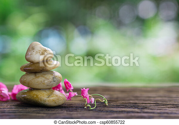 Balance Zen Stones And Pink Flower On Wood With Green Bokeh