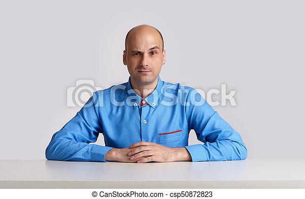 bald businessman sits at the desk - csp50872823