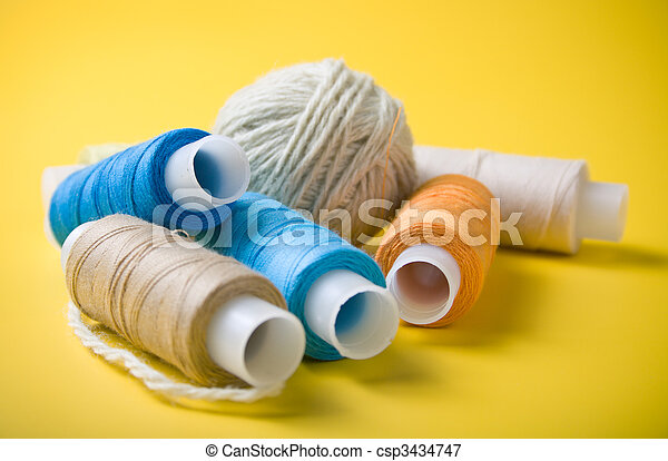 ball of yarn and spools of thread on a yellow background - csp3434747