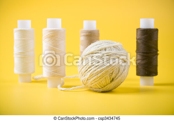 ball of yarn and spools of thread on a yellow background - csp3434745