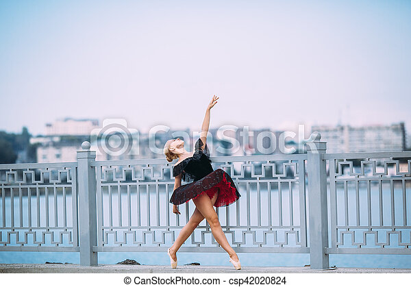 ballerina posing on a background of the lake - csp42020824