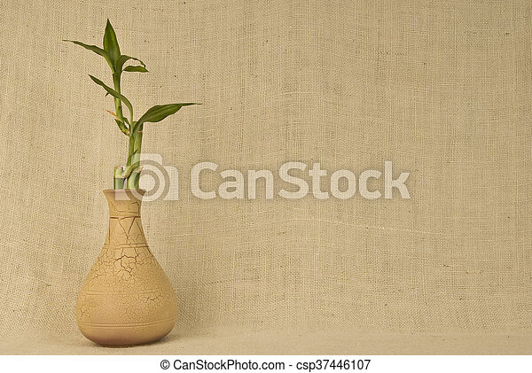 Horizontal Shot Of Bamboo In Vase On Burlap Background Copy Space