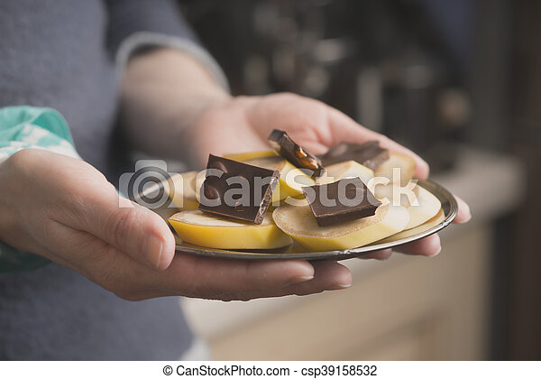 Banana and chocolate slices on the plate in the hand horizontal - csp39158532