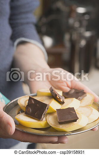 Banana and chocolate slices on the plate in the hand vertical - csp39158931