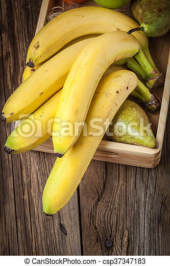 Bananas and other fruits in a wooden box. - csp37347183