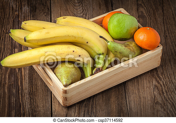 Bananas and other fruits in a wooden box. - csp37114592