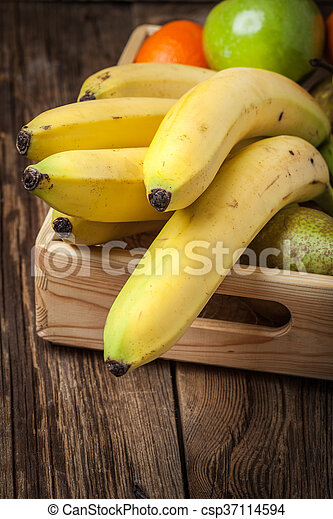 Bananas and other fruits in a wooden box. - csp37114594