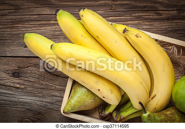 Bananas and other fruits in a wooden box. - csp37114595