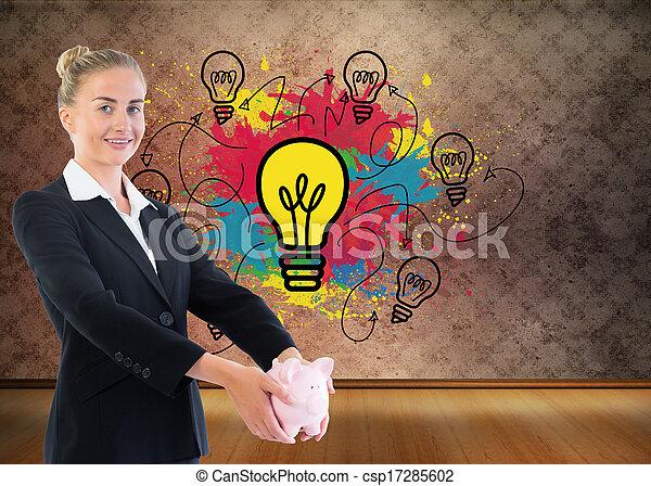 Imagen compuesta de una mujer de negocios sosteniendo una alcancía - csp17285602