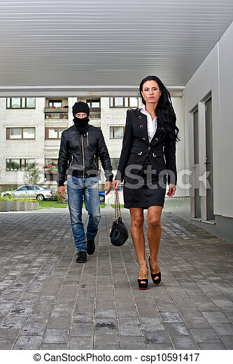 Bandit in mask following businesswoman. Robbery concept - csp10591417