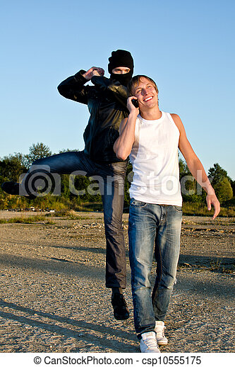 Bandit in mask trying to rob young man - csp10555175