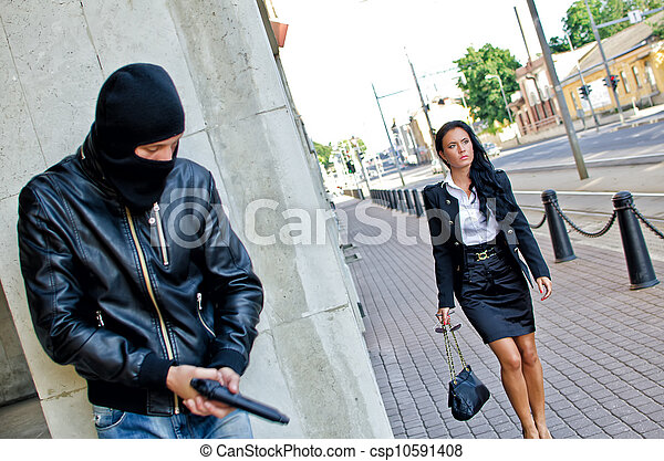 Bandit in mask with gun waiting for victim - csp10591408