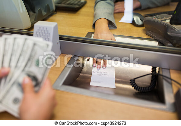 bank clerk giving receipt to customer with money - csp43924273