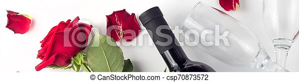 Banner of Bottle of wine, glass and red rose with petals on a white background - csp70873572