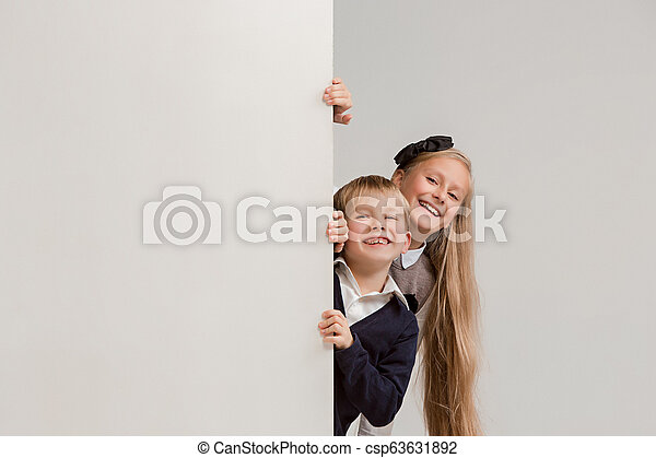 8887e6968b4 Banner with a surprised children peeking at the edge with copyspace. the  portrait of cute little kids boy and girls looking at camera against white  studio ...