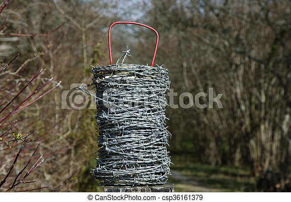 Barb wire roll with a natural background - csp36161379
