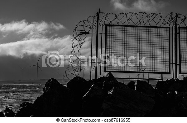 Barbed wire. Barbed wire fence near the sea. - csp87616955