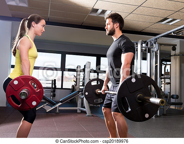 Barbell man and woman workout at fitness gym - csp20189976