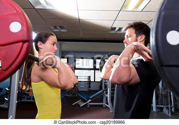 Barbell man and woman workout at fitness gym - csp20189966