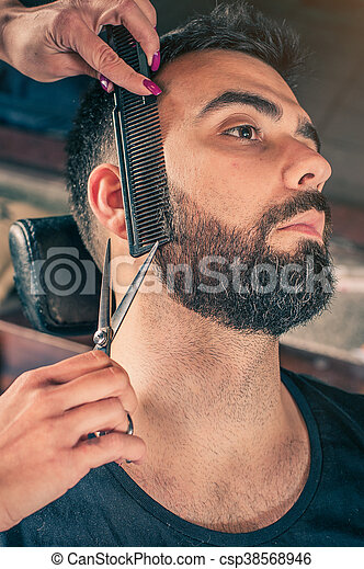 Barber beard cut a client's beard with clippers - csp38568946