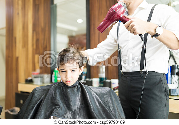 Barber Blow Drying Customer's Hair In Shop - csp59790169