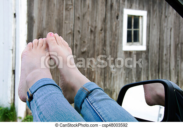 bare feet hanging out of car window - csp48003592