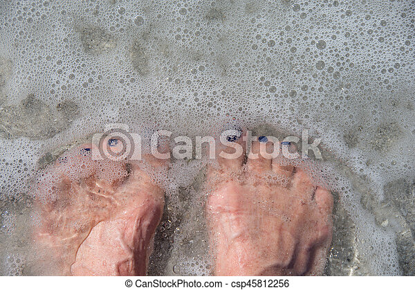 bare feet in ocean water - csp45812256