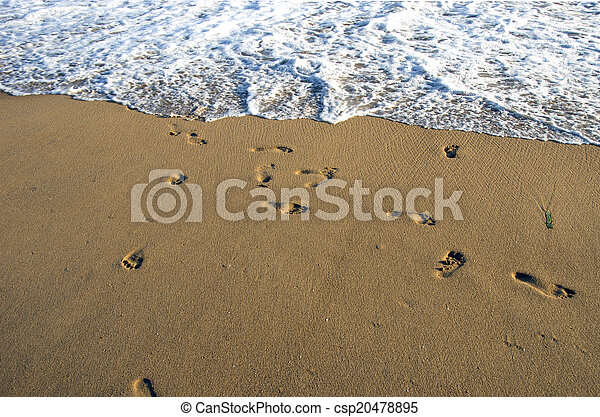 barefoot footsteps on ocean beach sand and wave - csp20478895