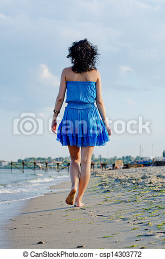 Barefoot woman walking on a beach - csp14303772
