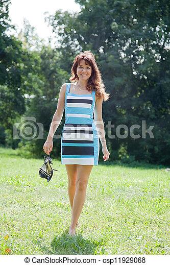 barefoot woman walking on lawn - csp11929068