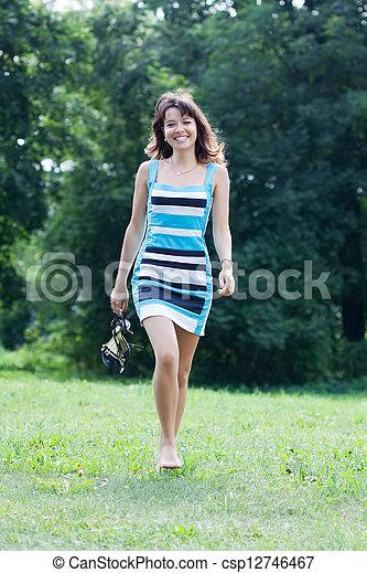 barefoot woman walking on lawn - csp12746467