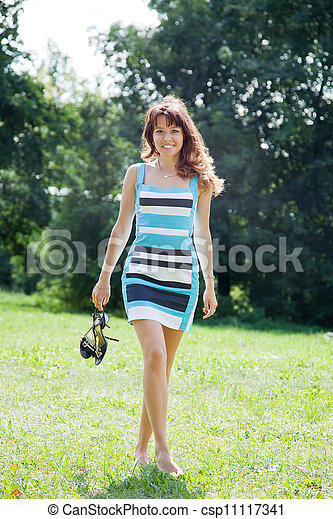 barefoot woman walking on lawn - csp11117341