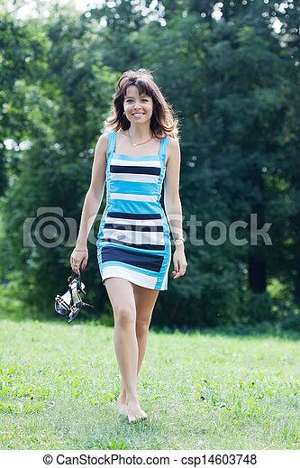 barefoot woman walking on lawn - csp14603748