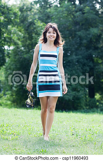 barefoot woman walking on lawn - csp11960493