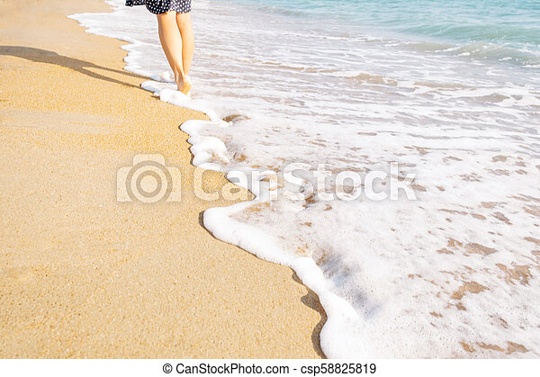 Barefoot young woman walking on sand beach. - csp58825819