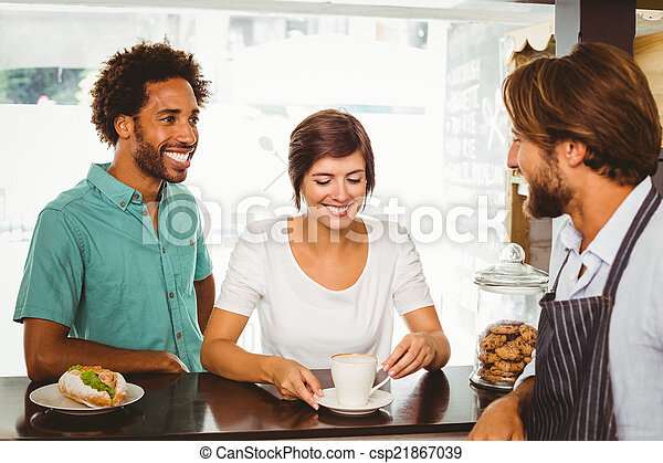 Barista talking with two customers - csp21867039