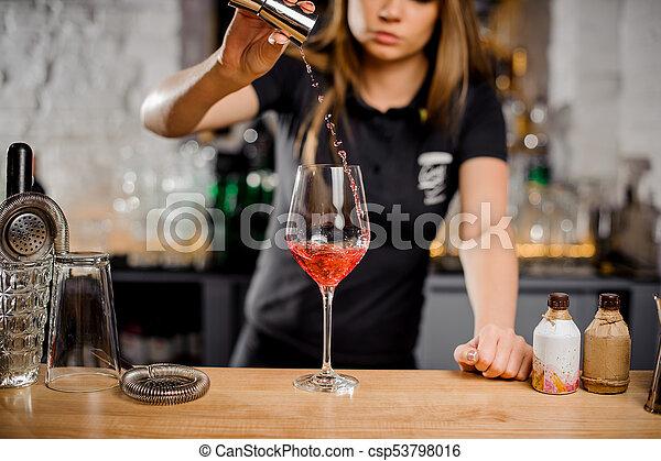 barmaid mixing cocktails at the bar counter using bar equipment - csp53798016