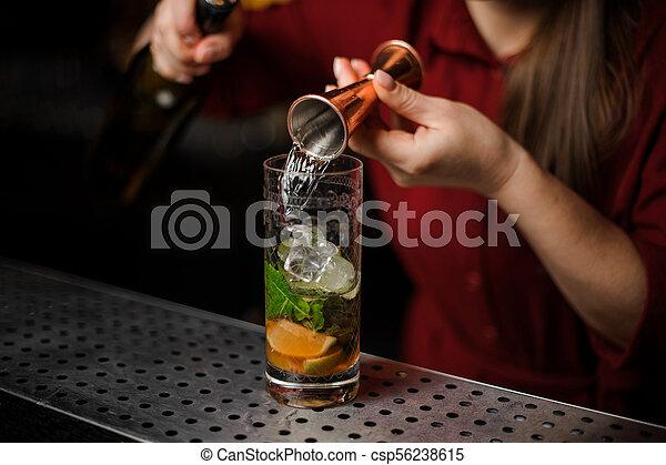 barmaid prepares a mojito, adding white rum - csp56238615