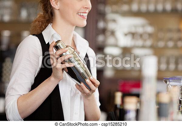Barmaid shaking a cocktail shaker - csp15285210