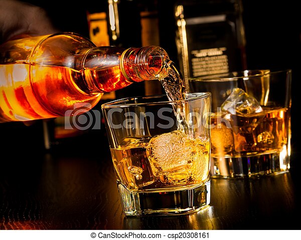 barman pouring whiskey in front of whiskey glass and bottles - csp20308161