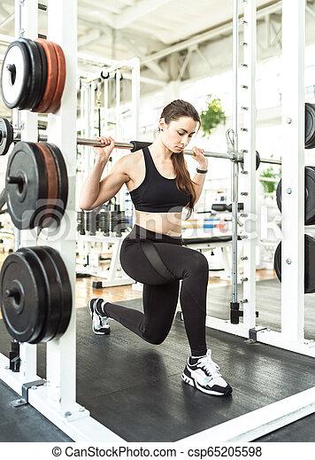 Chica en cuclillas en una rodilla con una pesa - csp65205598