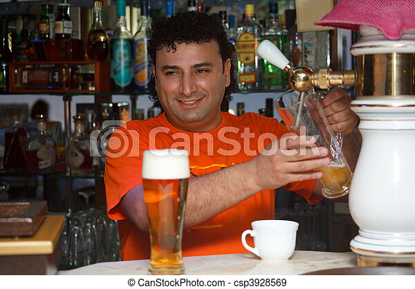 Bartender fills glass of beer. Smiling man against shelves with bottles. - csp3928569