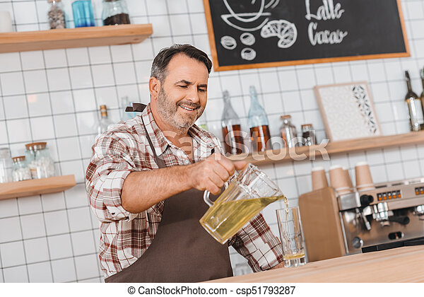 bartender pouring apple juice in glass - csp51793287