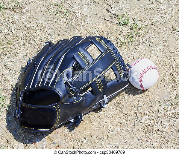 Baseball and glove over dirt - csp38469789