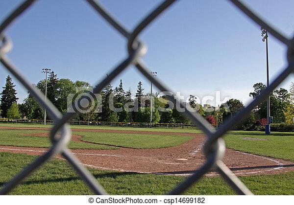 baseball field fence framing a shot of an unoccupied baseball field