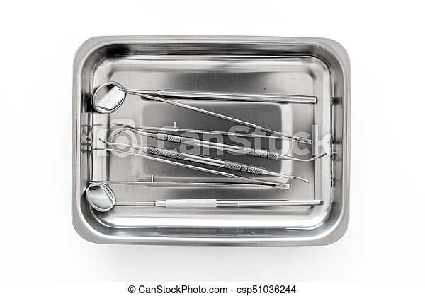 basic dentists tools in cuvette on white background top view
