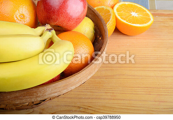 Basket of fruits on wooden table. - csp39788950